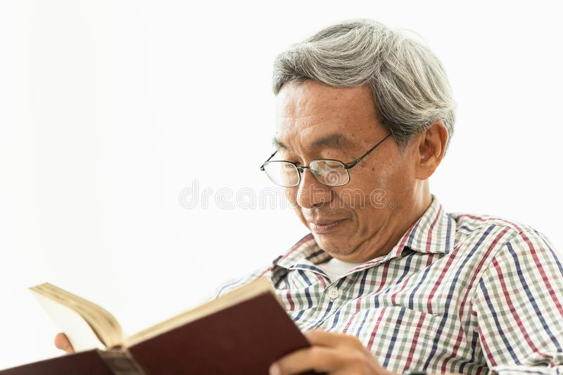 Asian Old man glasses professor amile reading textbook royalty free stock photo