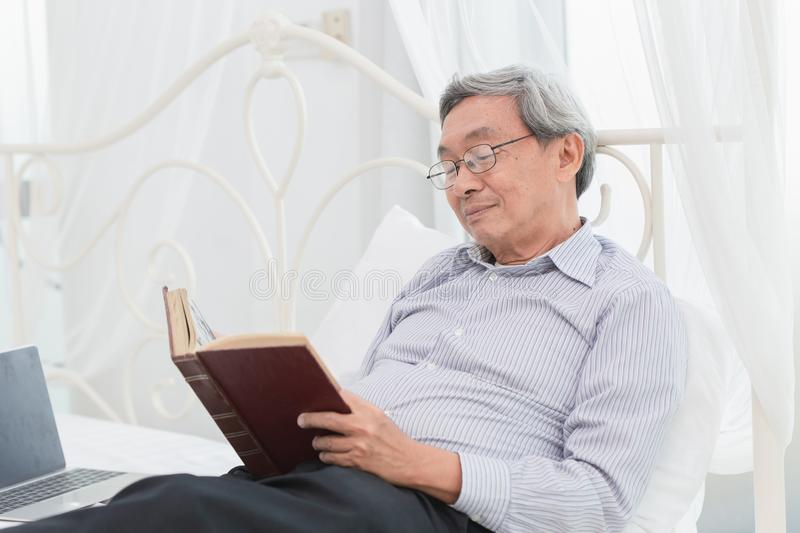 Asian Old man glasses professor enjoy reading textbook stock image