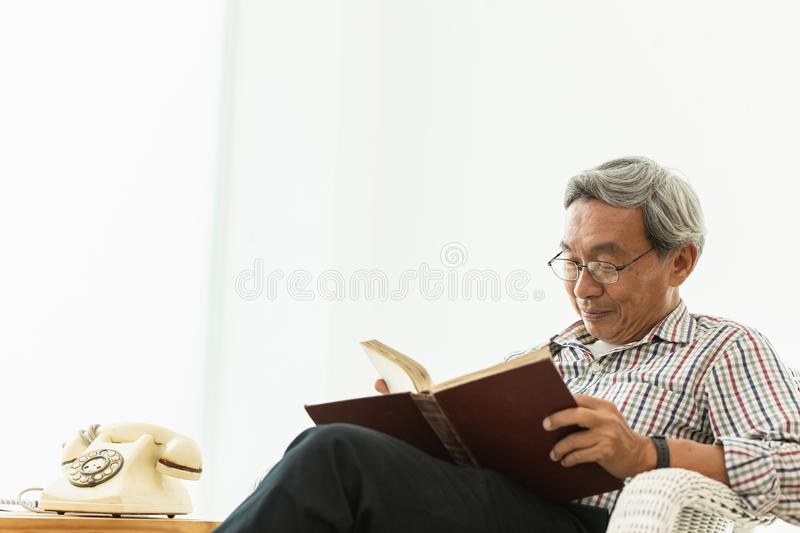 Asian Old man glasses professor sitting on the chair reading textbook stock images