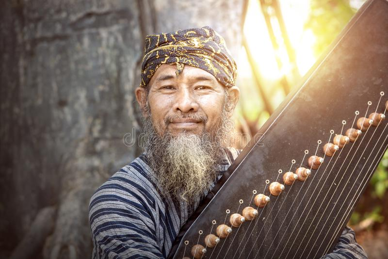 Asian old man holding kecapi with tree background. Kecapi is a traditional musical instrument of Indonesia stock photos