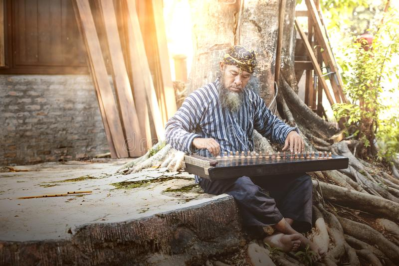 Asian old man playing kecapi with tree background. Kecapi is a traditional musical instrument of Indonesia royalty free stock photo