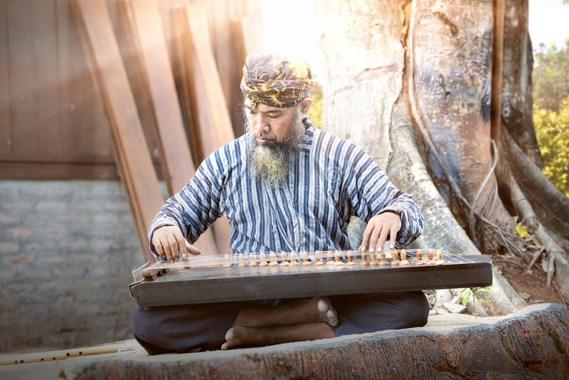 Asian old man playing kecapi with tree background. Kecapi is a traditional musical instrument of Indonesia stock photography