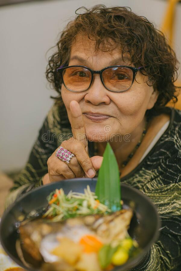 Asian old woman tourist face camera smiling fork in hand showing local food or Japanese food.  stock photos