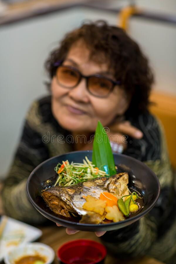 Asian old woman tourist face camera smiling fork in hand showing local food or Japanese food.  stock image