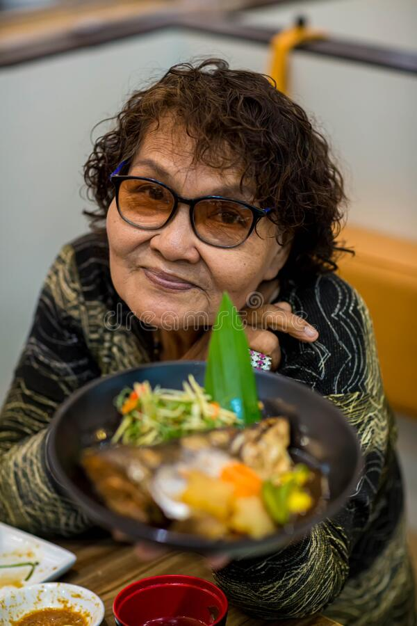 Asian old woman tourist face camera smiling fork in hand showing local food or Japanese food.  royalty free stock photo