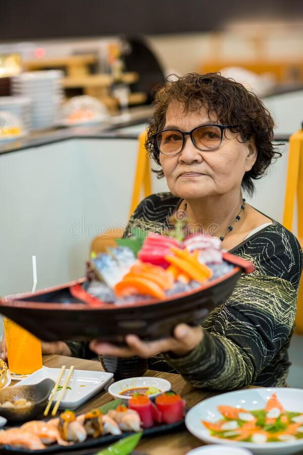 Asian old woman tourist face camera smiling fork in hand showing local food or Japanese food. A woman aged and will show you sus. Asian old woman tourist face royalty free stock image