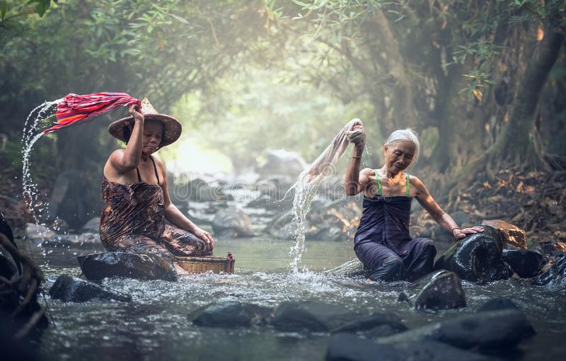 Asian old women washing clothes. At the creek stock photos