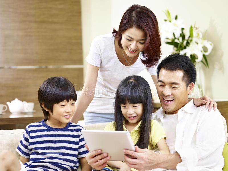 Asian family with two children using digital tablet together. Asian parents mother and father and two children son and daughter sitting on family couch using stock photo