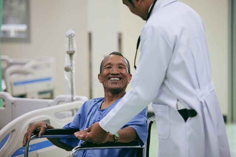 Asian patient in wheelchair sitting in hospital with Asian doctor. stock photo