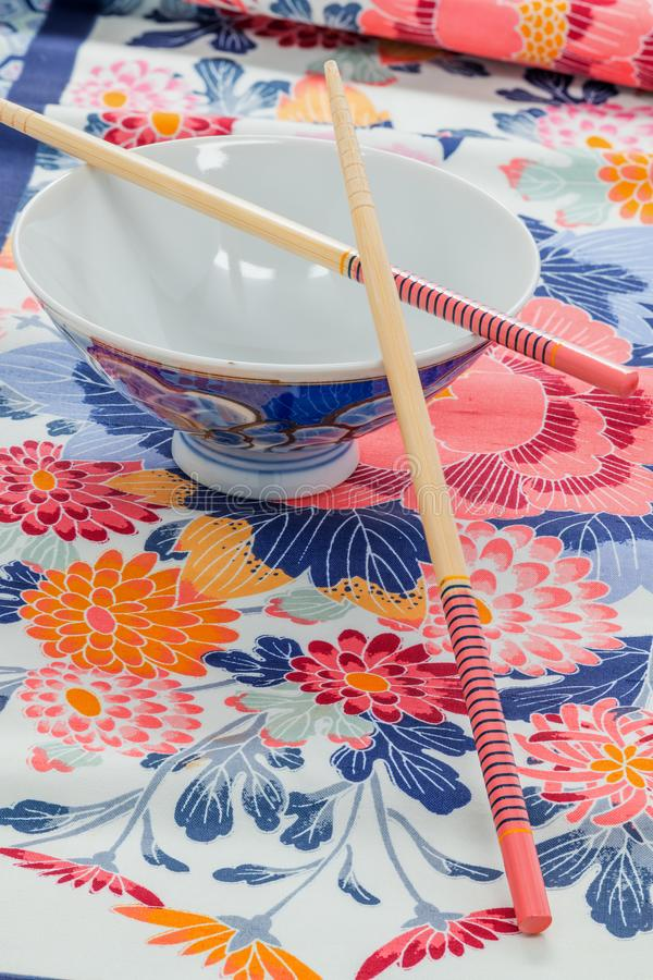 Chinese rice bowl with two chopsticks on a printed cloth royalty free stock photo