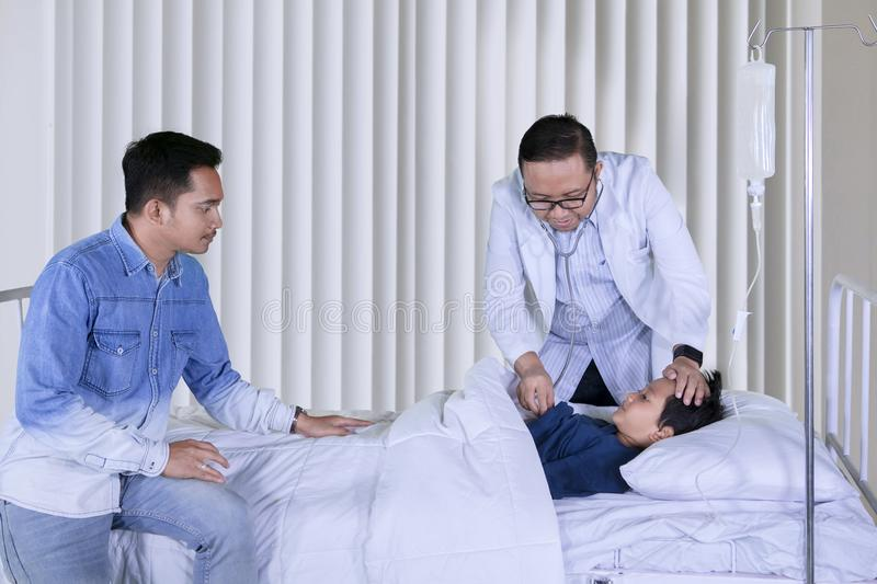 Asian pediatrician examines his patient in the clinic royalty free stock images