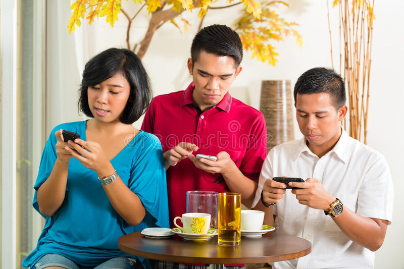 Asian people having fun with mobile phone stock photos
