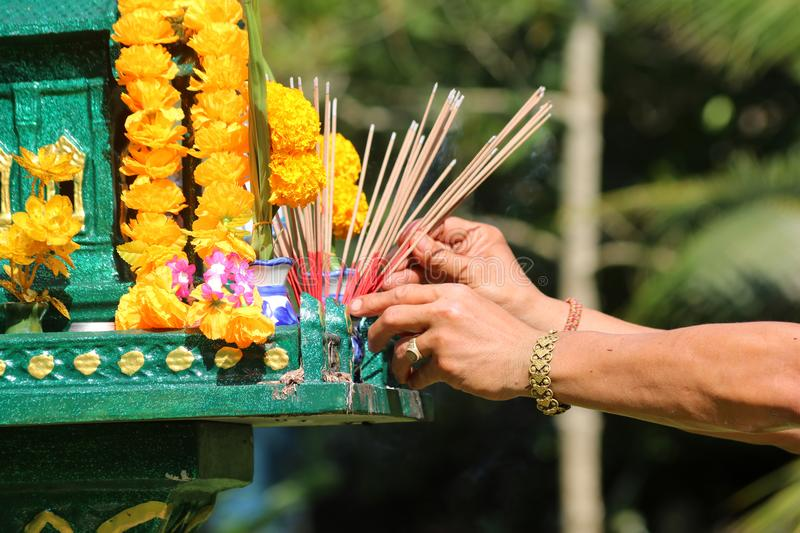 Asian people with incense pay respect to shrine or spirit worship. Asian people pay respect to shrine of the household god or spirit worship, and firecrackers royalty free stock image
