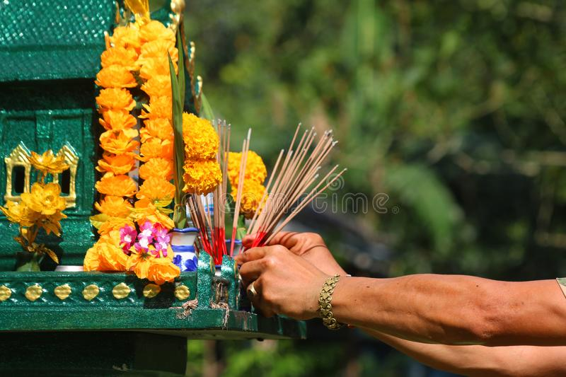 Asian people with incense pay respect to shrine or spirit worship. Asian people pay respect to shrine of the household god or spirit worship, and firecrackers stock image
