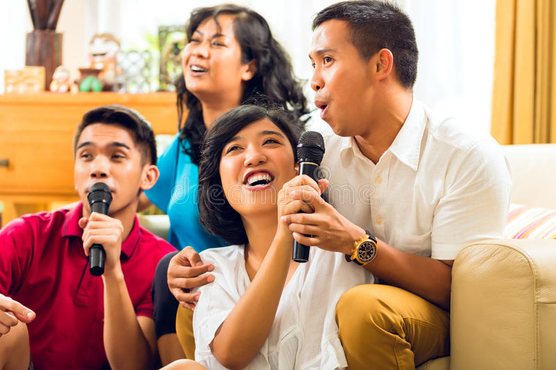 Asian people singing at karaoke party royalty free stock photos