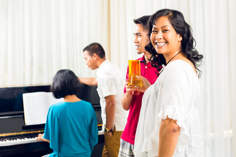 Asian people sitting together at the piano royalty free stock images