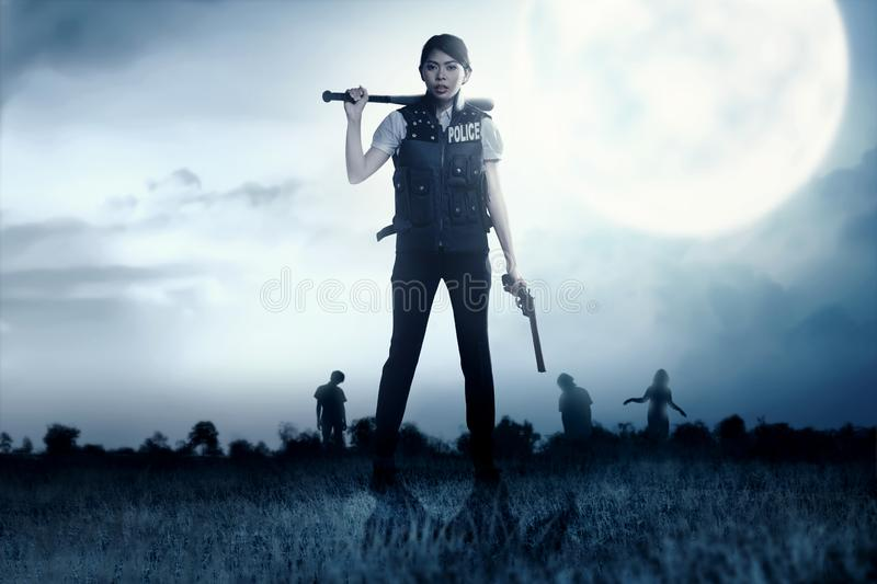 Asian policewoman with the gun and baseball bat in her hand face the zombies on the grass field royalty free stock photography