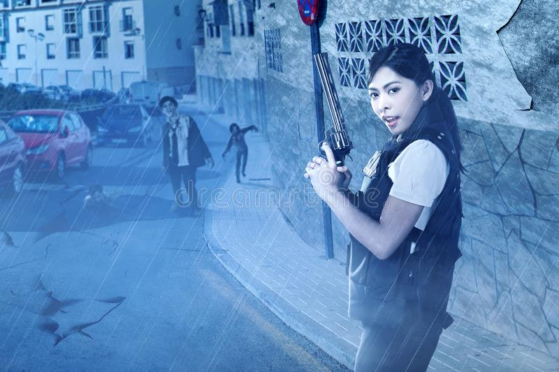 Asian policewoman with the gun on her hand face the zombies on the abandoned city stock images