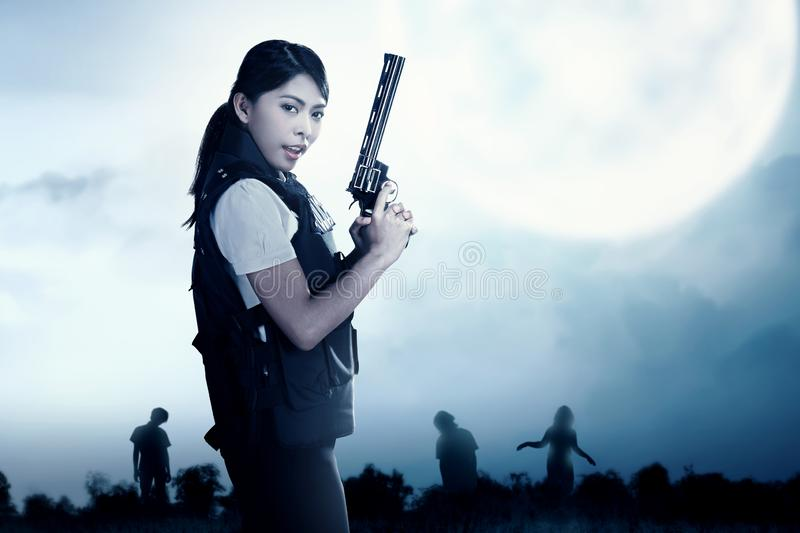Asian policewoman with the gun on her hand face the zombies on the grass field stock images