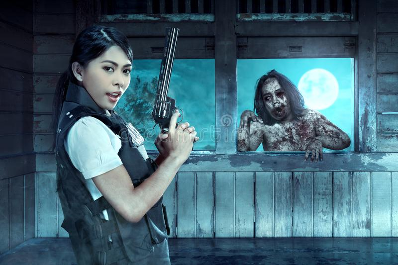 Asian policewoman with the gun on his hand face the zombies on the old wagon stock image