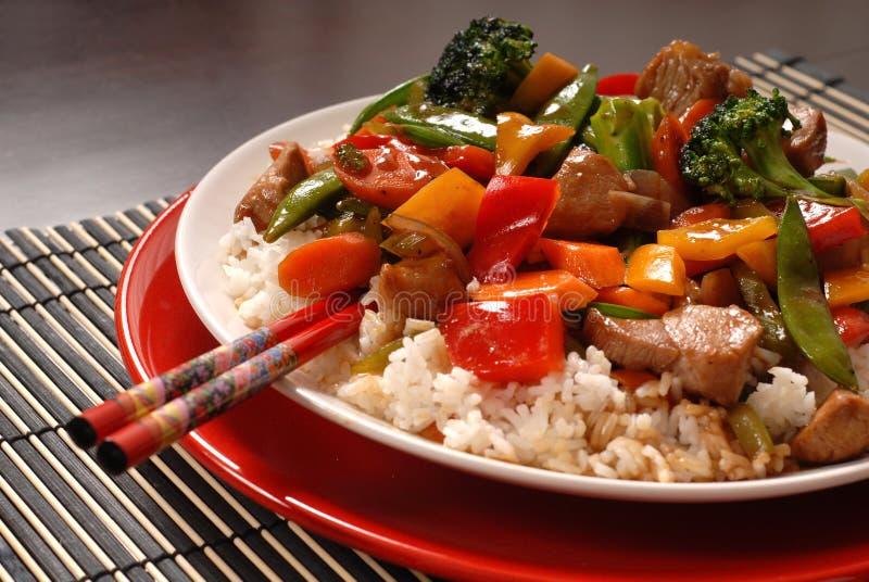 Asian pork stir fry. An Asian pork stir fry with chop sticks stock images
