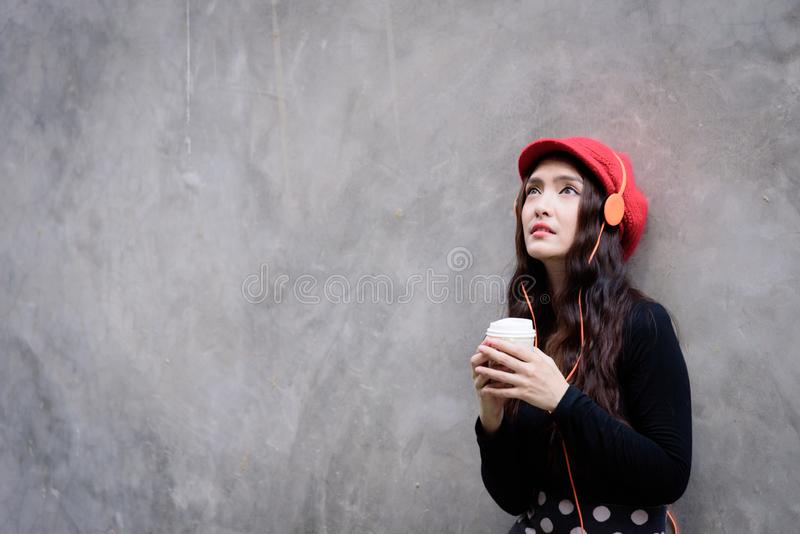 Asian portrait woman with red hat and black clothes has holding a cup of coffee with happiness and the grey stone wallpaper royalty free stock image