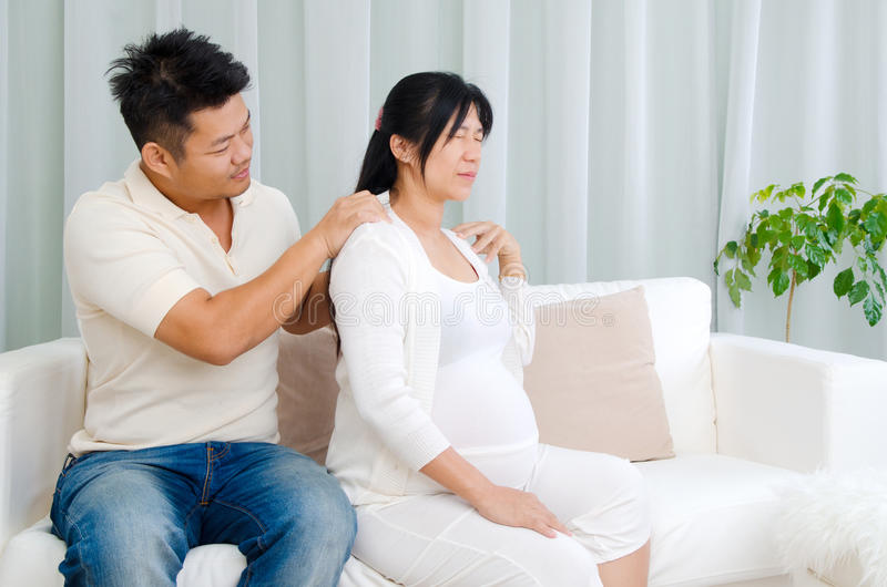 Asian pregnant couple. Asian husband massage for his pregnant wife who suffered shoulder pain stock photos