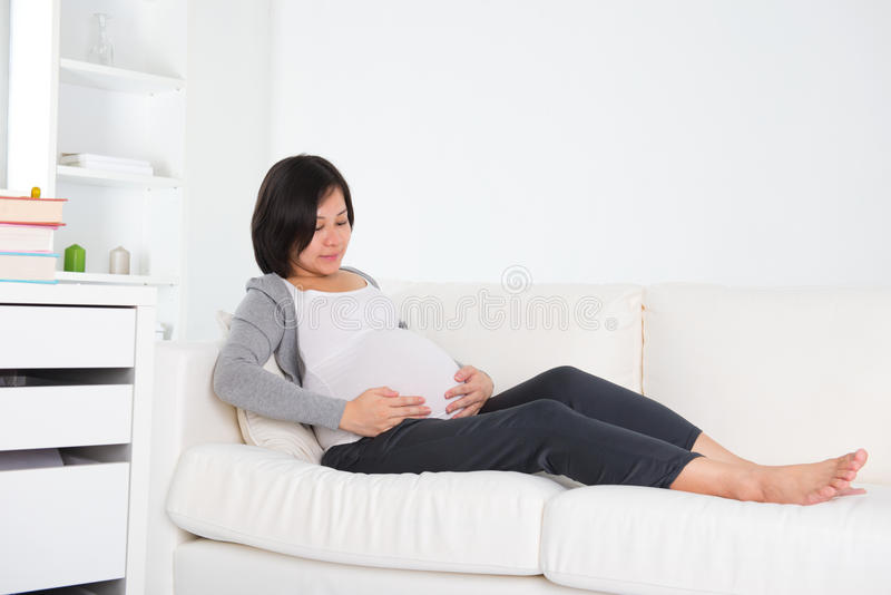 Asian pregnant mother sitting on couch. Photo royalty free stock photo