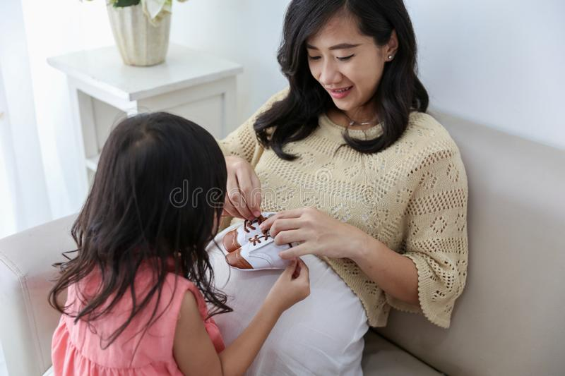 Asian pregnant mother takes her child stock photo