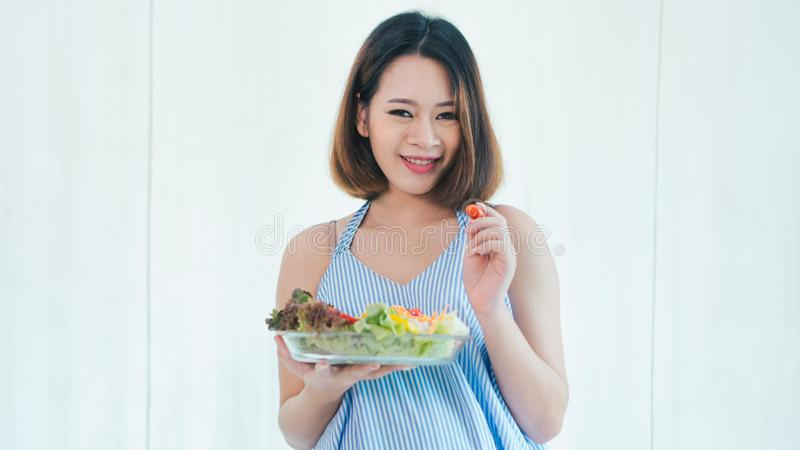 Asian pregnant woman is eating salad. stock photo