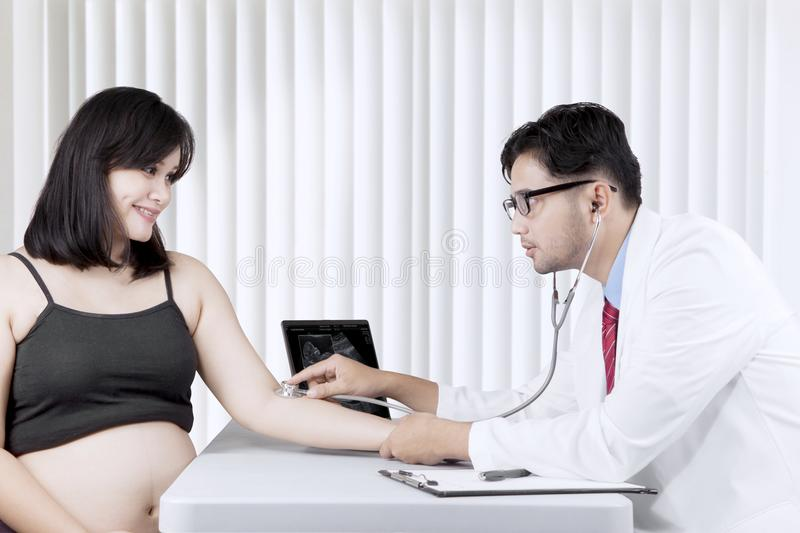 Asian pregnant woman having a consultation with a gynecologist. Asian pregnant women talking to a gynecologist in a clinic stock photos