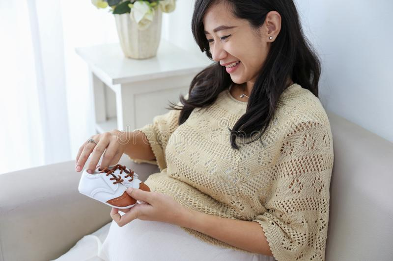 Asian pregnant woman holding baby shoes royalty free stock images