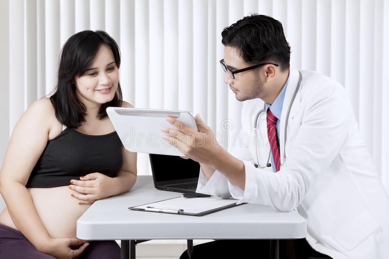 Asian pregnant woman having a consultation with a gynecologist. Asian pregnant women talking to a gynecologist in a clinic stock image