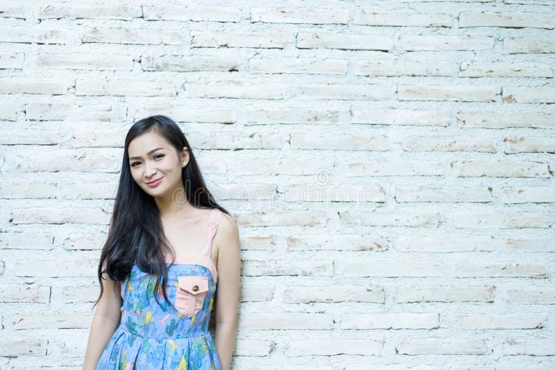 Asian pretty girl has posing hipster concept with brick background at Little Tree Garden cafe, Nakhon Pathom province, Thailand i royalty free stock photography