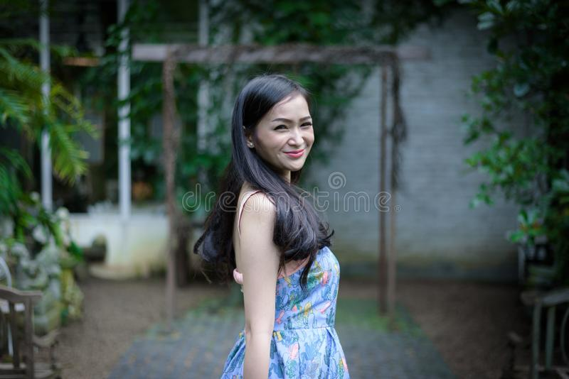 Asian pretty girl has relaxing with happy and smiling at Little Tree Garden cafe, Nakhon Pathom province, Thailand in the morning royalty free stock photography