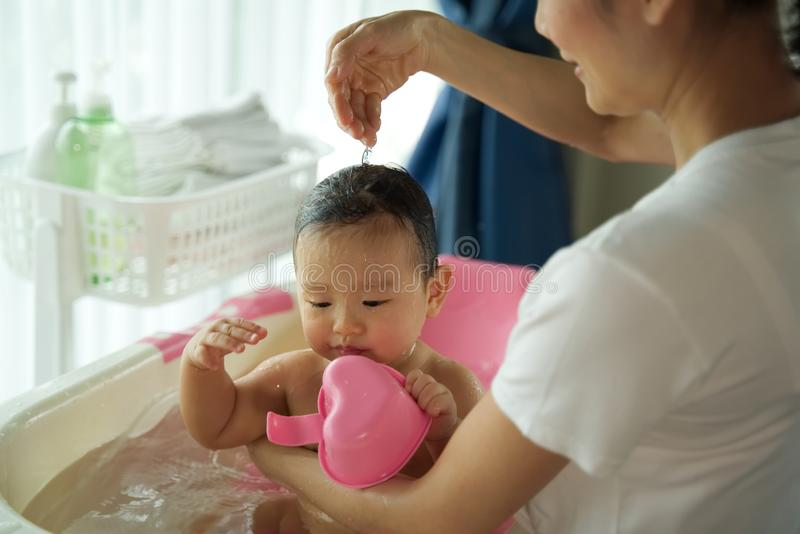 Asian pretty mother holding little cute baby and shampooing her child sitting in bathtub in the room. royalty free stock photography