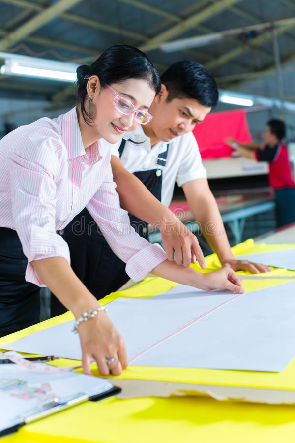 Asian production manager and designer in factory stock photography
