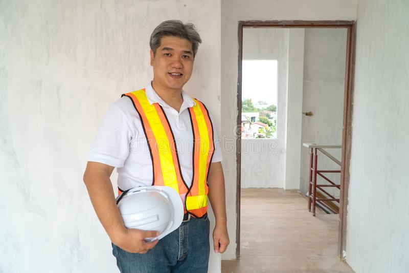 Asian professional engineer working in house construction site for inspection of the cottage under construction.  royalty free stock photos