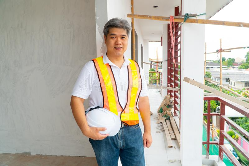 Asian professional engineer working in house construction site for inspection of the cottage under construction.  royalty free stock photography