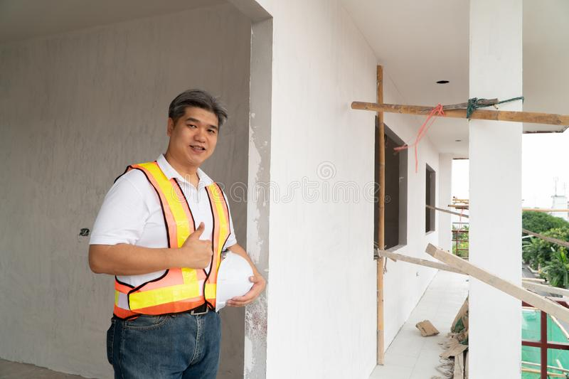 Asian professional engineer workering in house construction site for inspection of the cottage under construction and lift the thu. Mb up royalty free stock images
