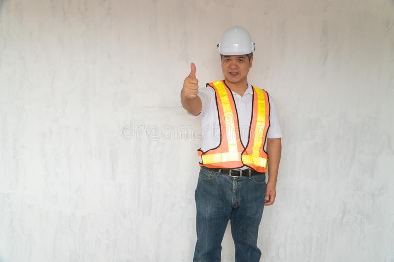 Asian professional engineer working in house construction site for inspection of the cottage under construction and lift the thu. Mb up stock photo