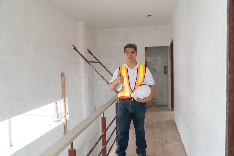Asian professional engineer working in house construction site for inspection of the cottage under construction and lift the thumb. Up stock photography