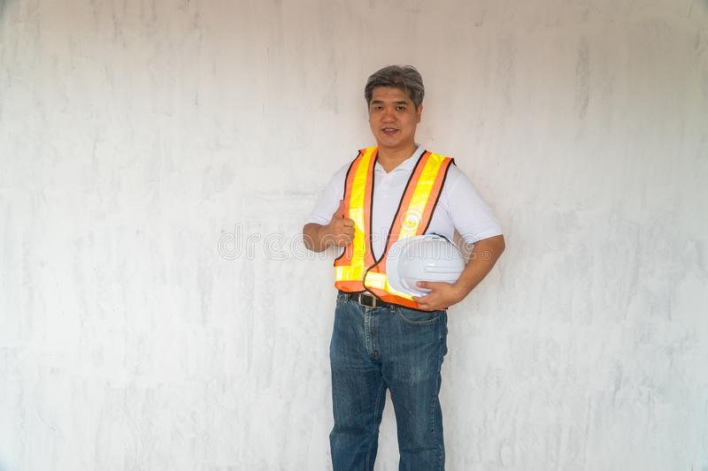 Asian professional engineer working in house construction site for inspection of the cottage under construction and lift the thumb. Up stock photo