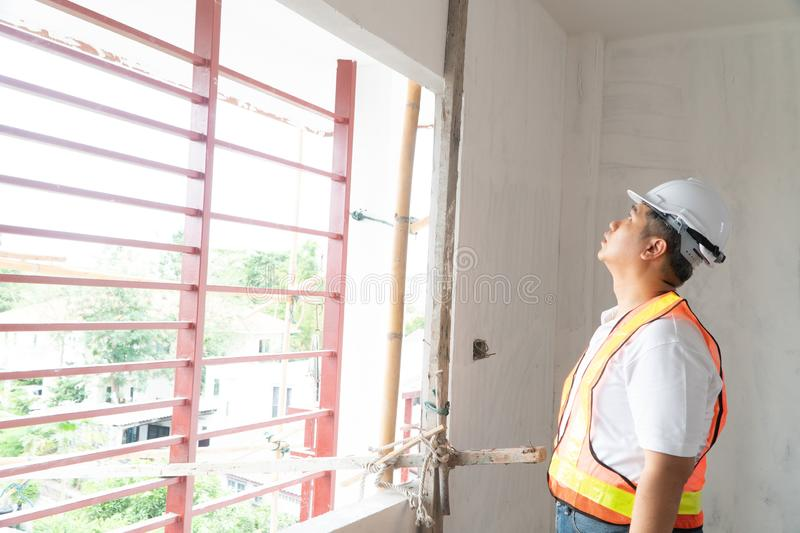 Asian professional engineer working in house construction site for inspection of the home under construction.  stock photo