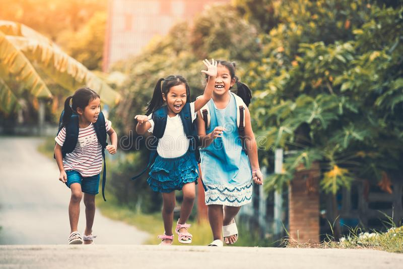 Asian pupil kids with backpack running stock image