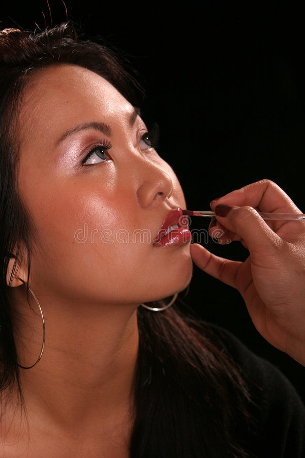 Asian putting on makeup royalty free stock photo