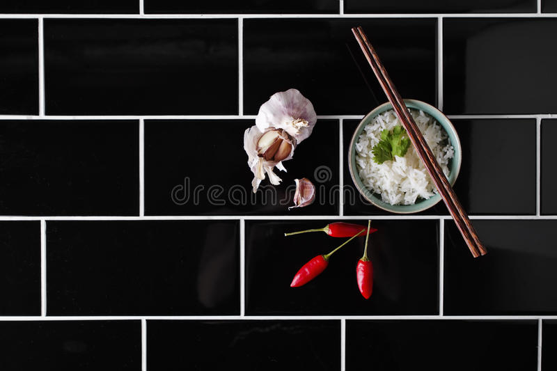 Asian rice dish and ingredients on black railway tiles. Asian rice dish and ingredients on black railway tile background stock photo