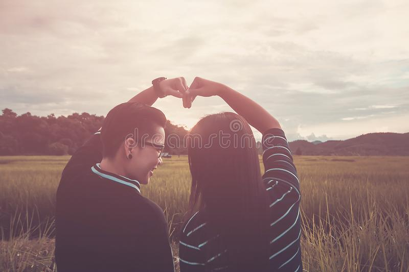 Asian,Romantic couple or Homosexuality, female love open arm , Heart signs happy on rice field with sunset, Valentine`s Day love. Concept royalty free stock photography