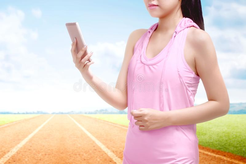 Asian runner woman using a mobile phone at the break after running on the running track stock images