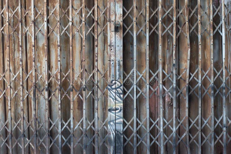 Asian rusty folding doors or traditional gate. Old steel rusty door texture pattern. Folding door texture pattern and background with graffiti on handle stock image